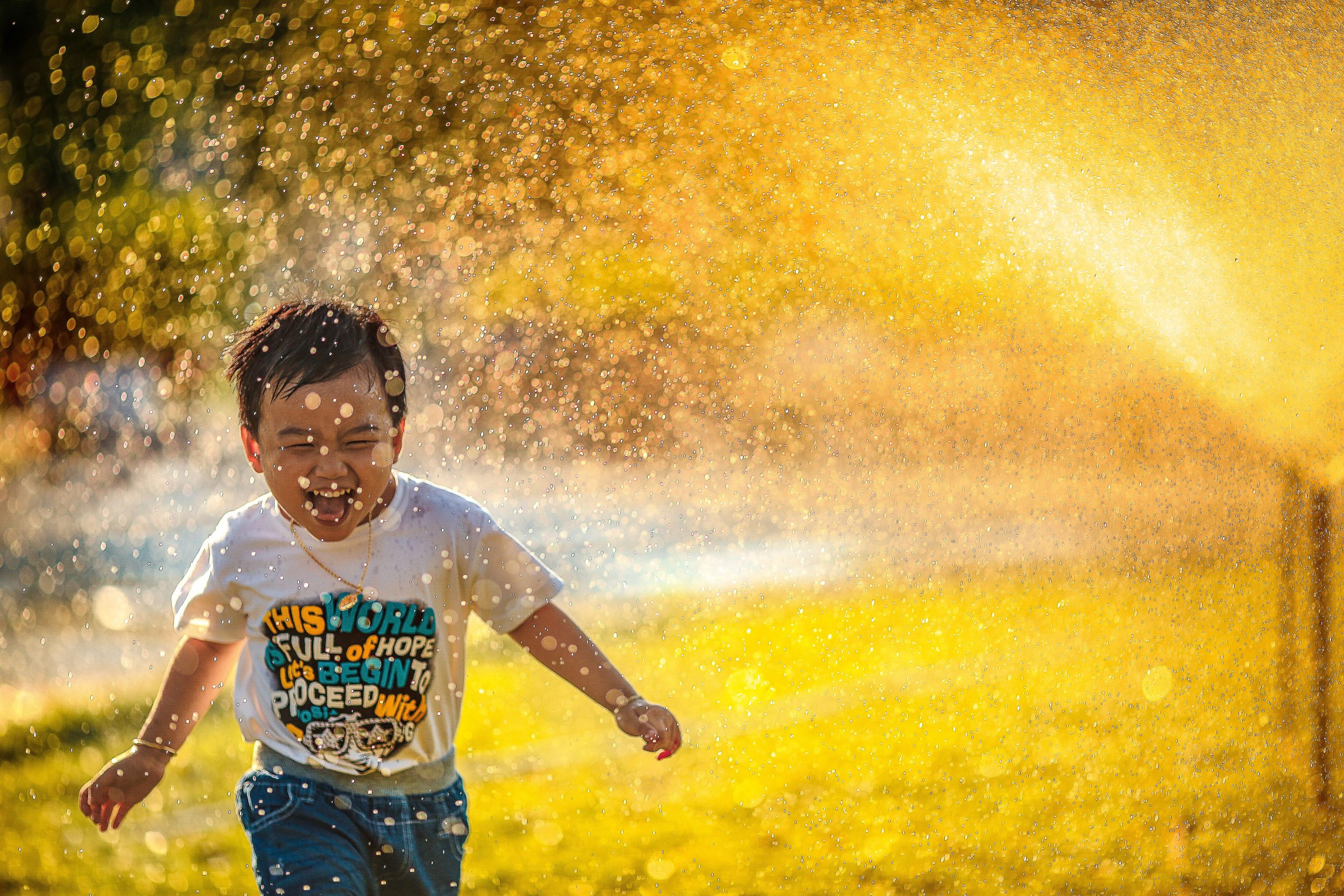 Boy running through sprinkler relating to things kids can teach us about business.